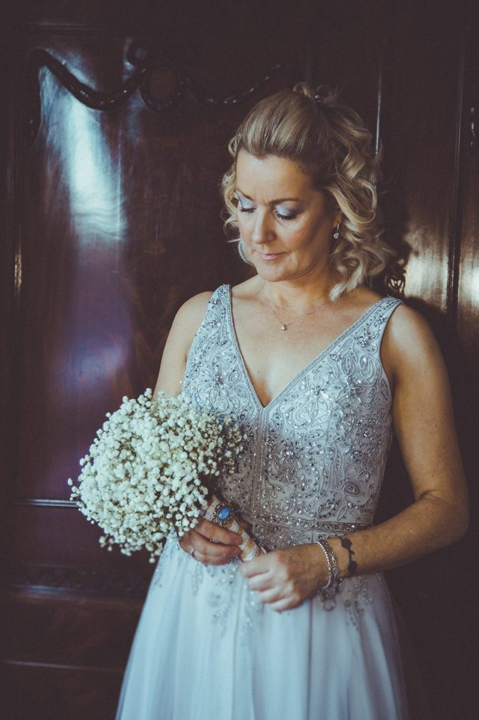 The bride looking at here bouquet at Horton Grange Hotel in Northumberland