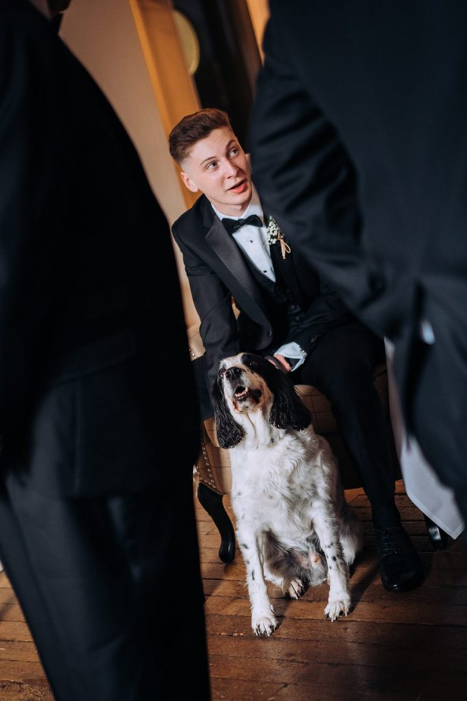 Brides son holding their pet spaniel