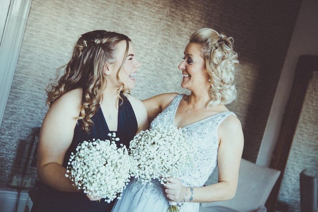Bride & bridesmaids laughing at each other at Horton Grange Hotel in Northumberland