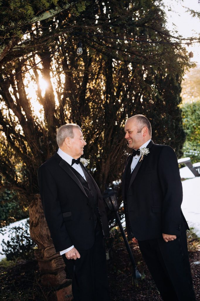 Groom talking to brides father in the grounds of Horton Grange Hotel in Northumberland