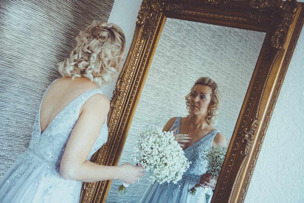 Bride checking her necklace in the mirror at Horton Grange Hotel in Northumberland