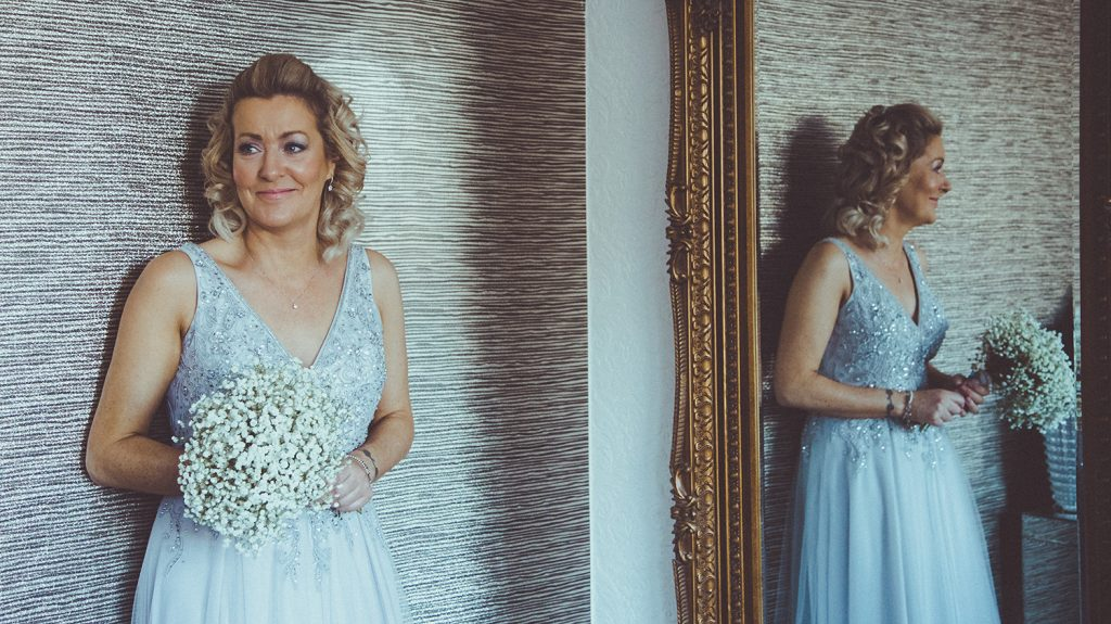 bride smiling against the wall at Horton Grange Hotel in Northumberland