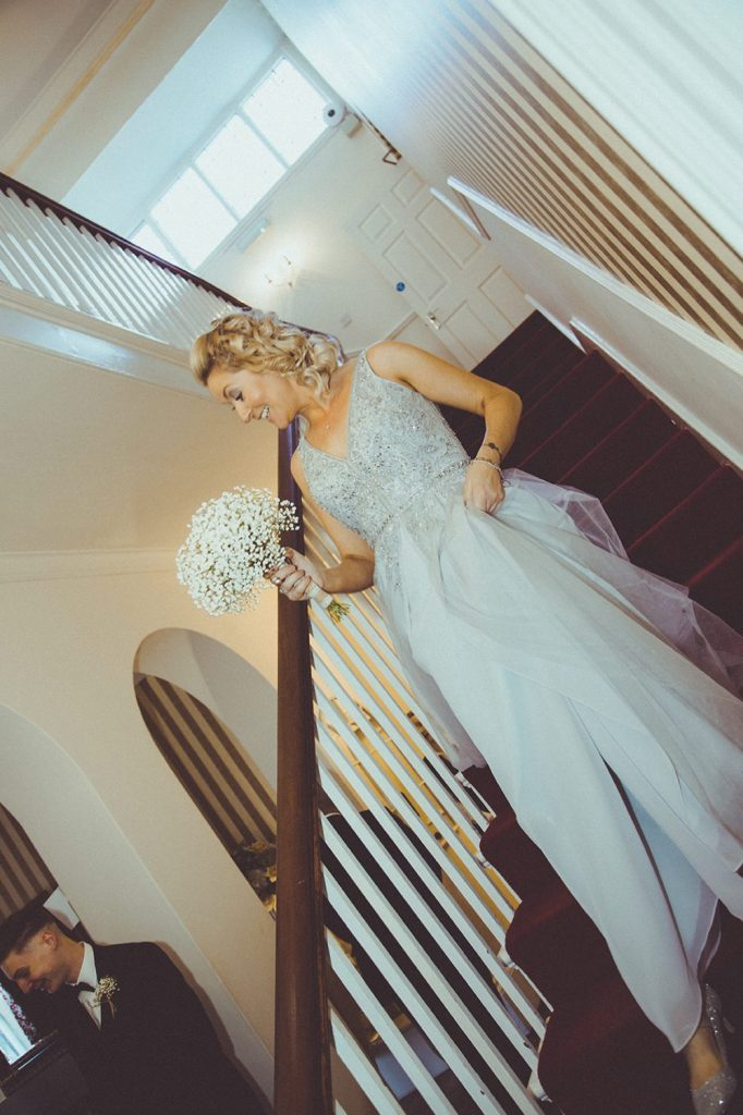 Bride walking do the stairs of Horton Grange Hotel in Northumberland