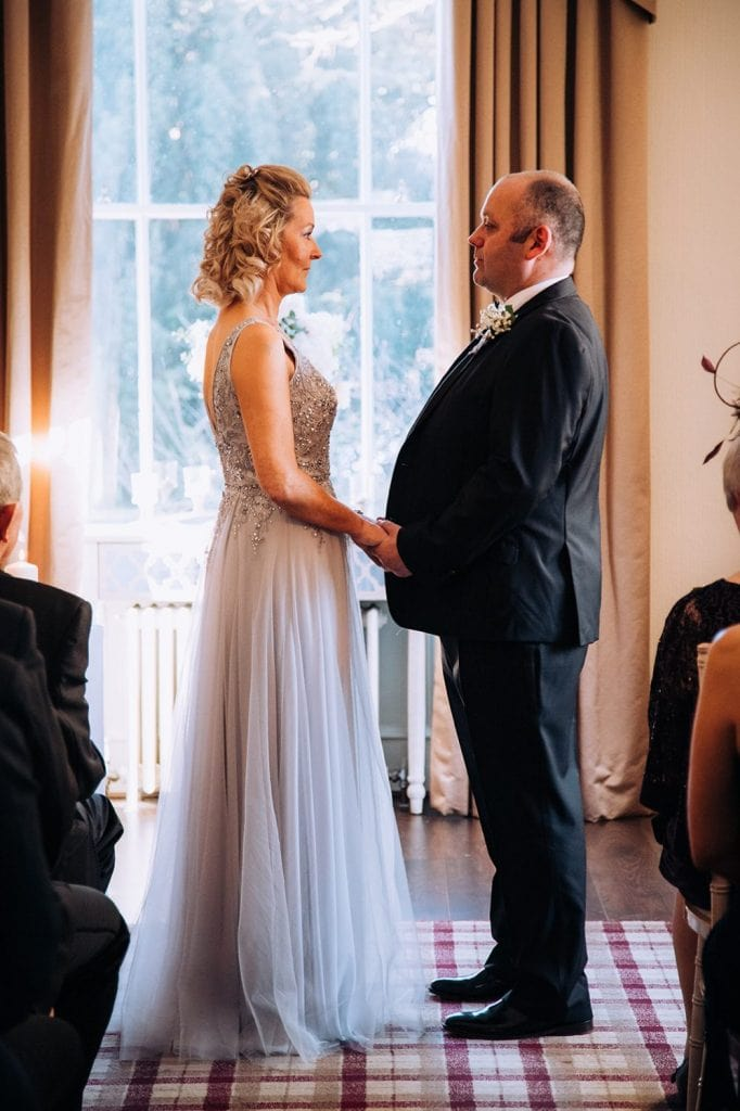 Carl & Jo facing each other during the wedding service at Horton Grange