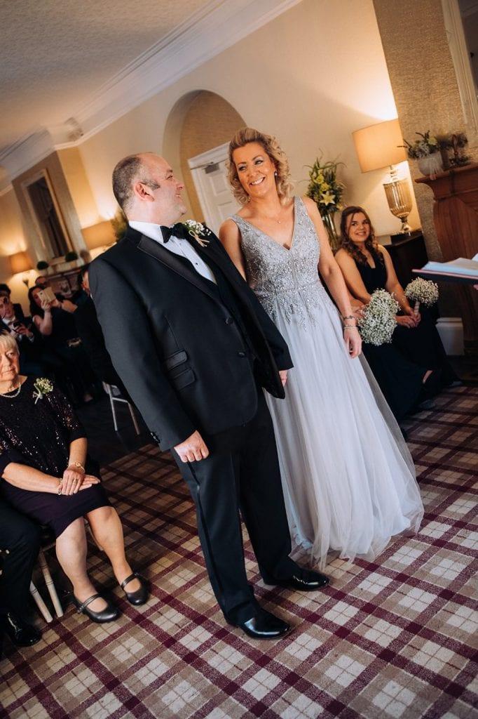 Jo & Carl laughing during wedding service at Horton Grange