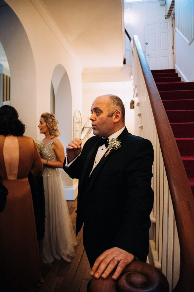 Groom having a sneaky drink at The Horton Grange Hotel