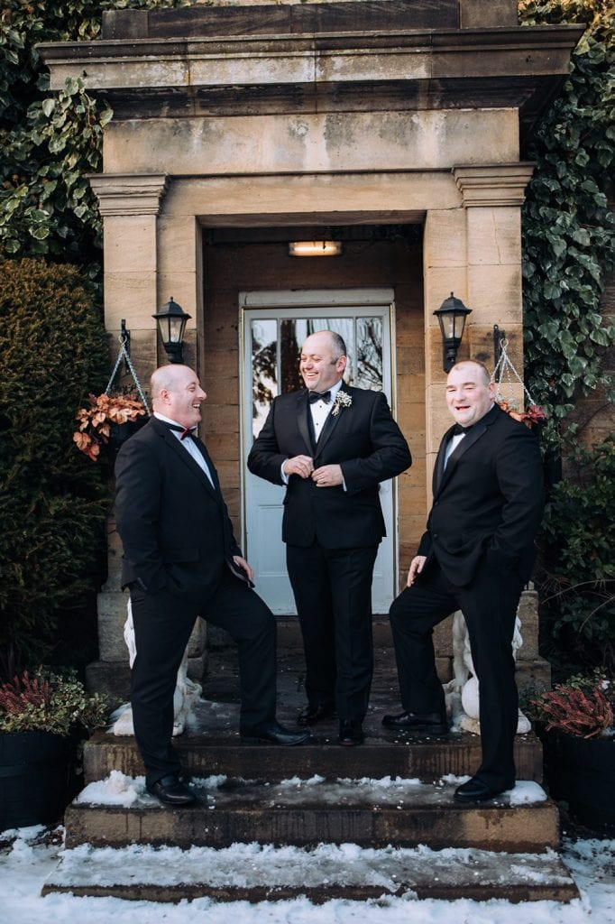 Groom joking with his friends outside Horton Grange Hotel
