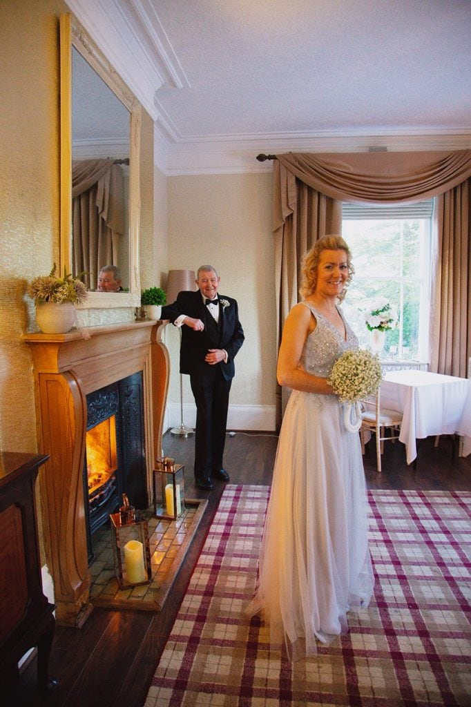 Bride and father of the bride warming themselves infont of the fire at Horton Grange Hotel