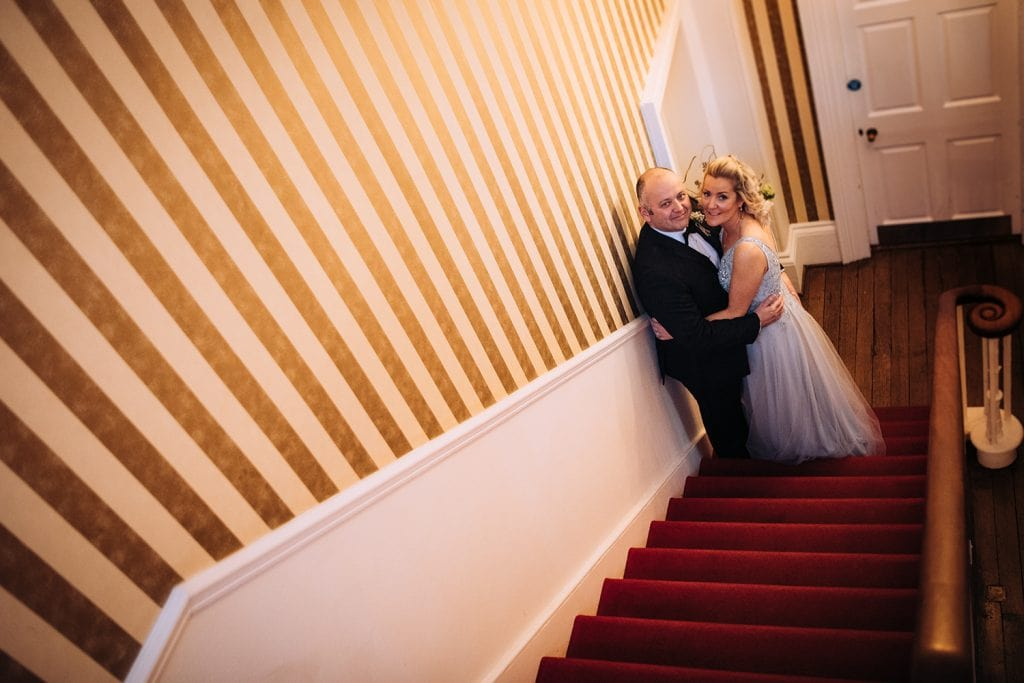 The Bride & Groom Hugging on the stairs at Horton Grange