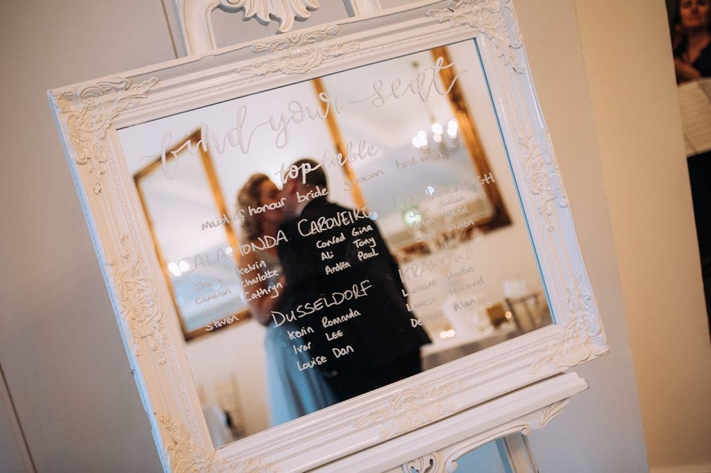 Reflection of the Bride & Groom in the table plan mirror at Horton Grange in Northumberland