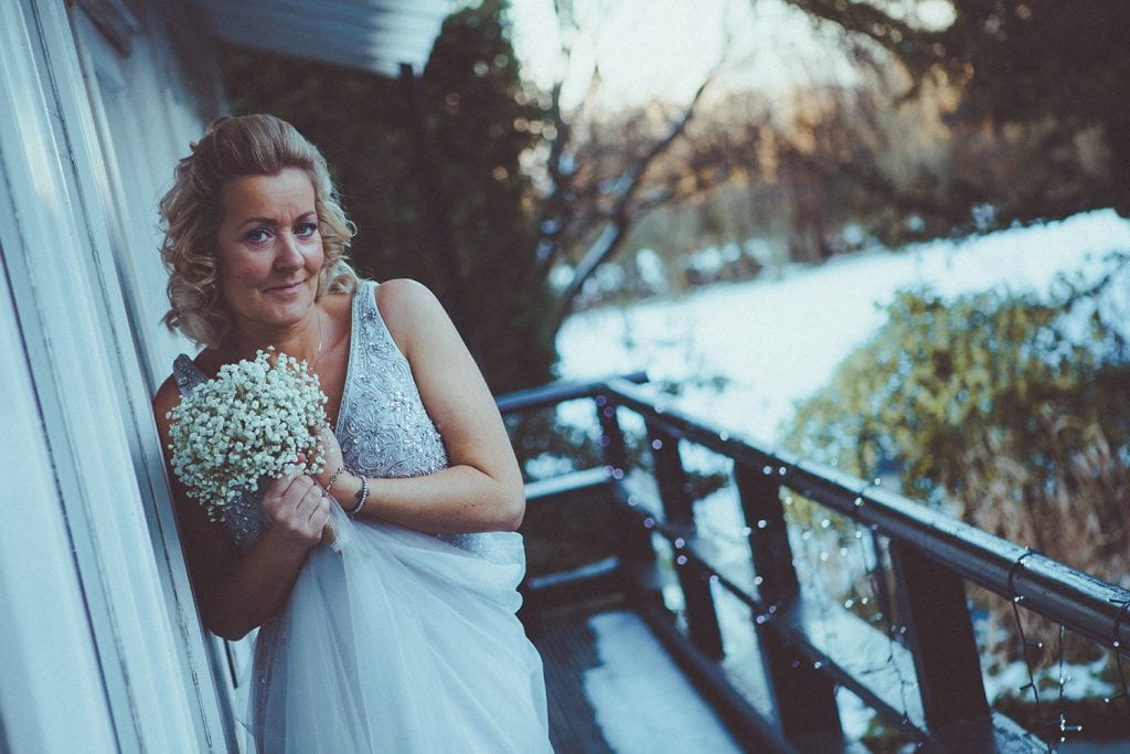 The bride keeping warm in the snow at Horton Grange in Northumberland