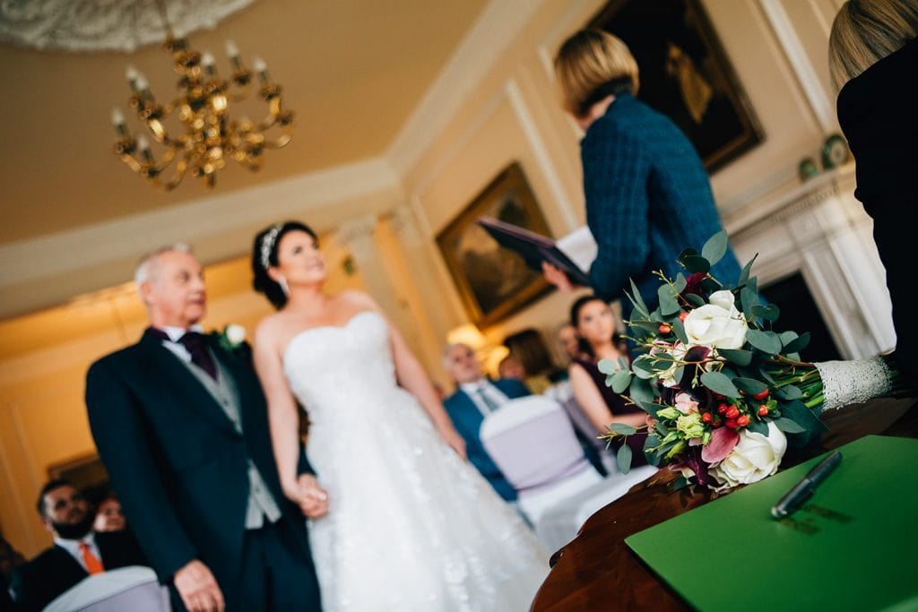 The brides bouquet in focus with the couple behind