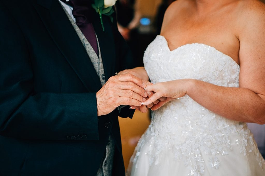 Groom placing a ring on his brides finger