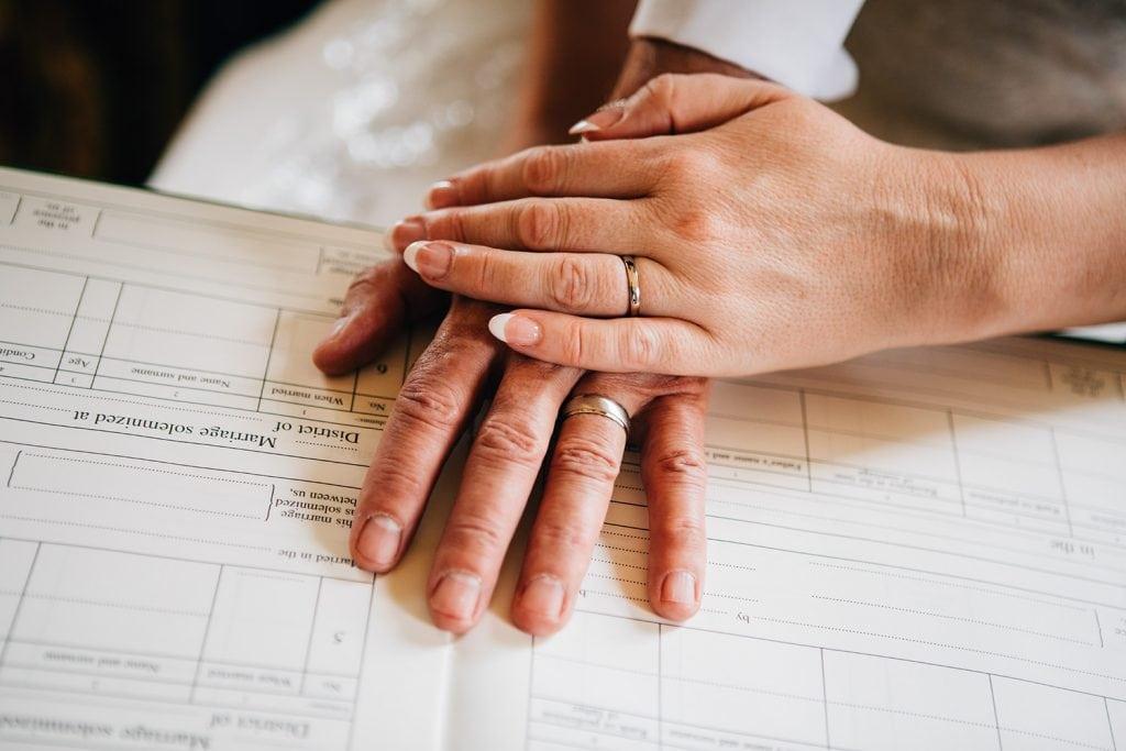 Bride & Grooms hands & rings on the wedding register