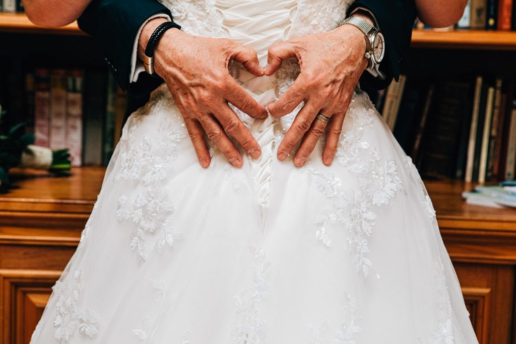 Grooms hands in the shape of a heart