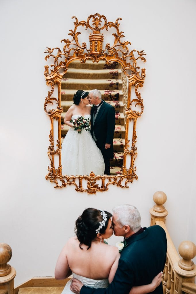 Bride & Groom reflected in the staircase mirror at Doxford Hall