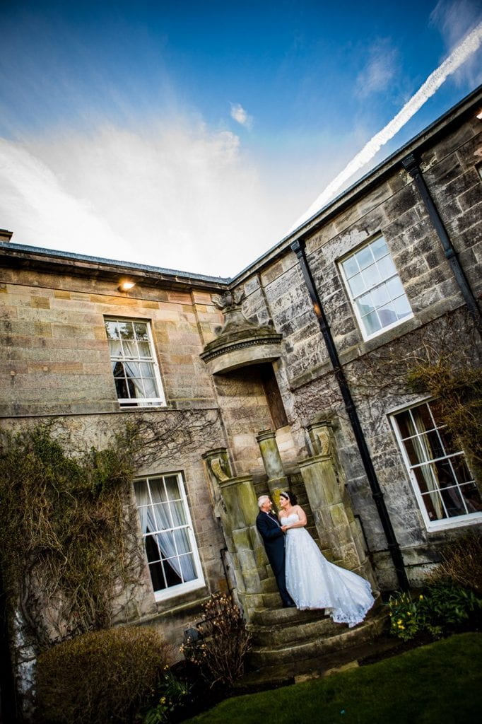 Michael & Kerry hugging on the steps outside of Doxford Hall in Northumberland