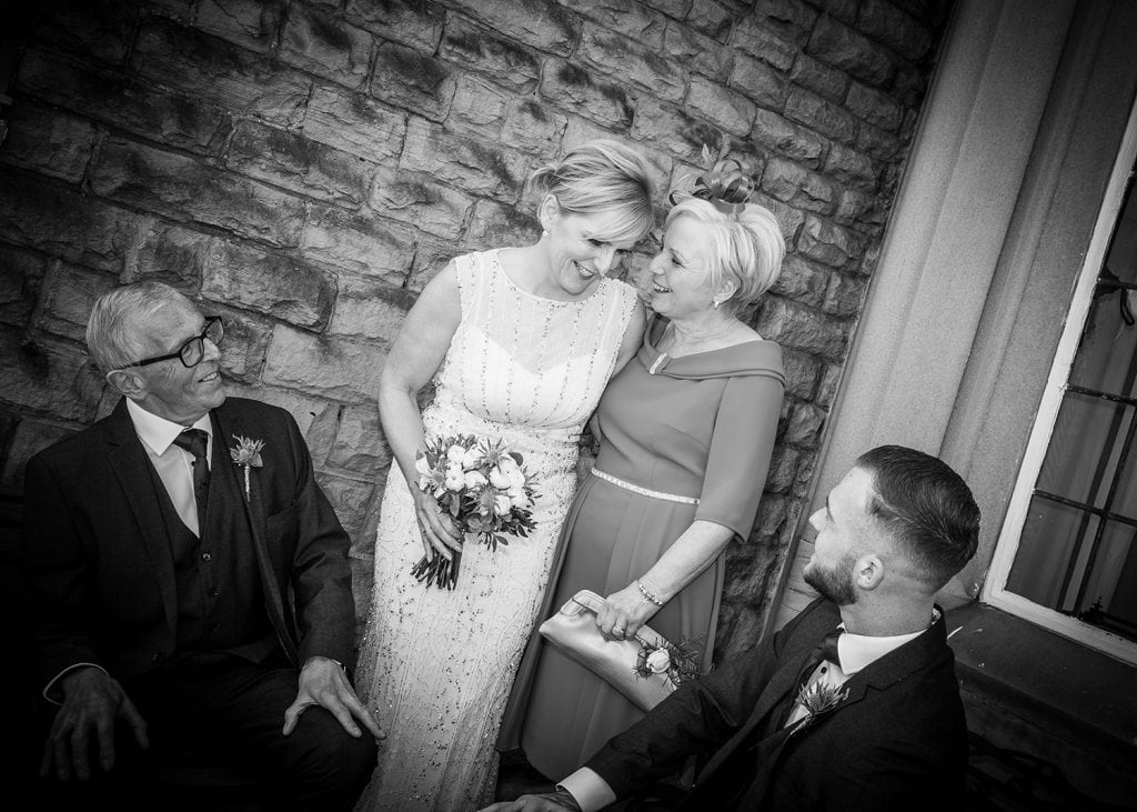 Bride joking with her family on the balcony of The Mansion House in Jesmond, Newcastle