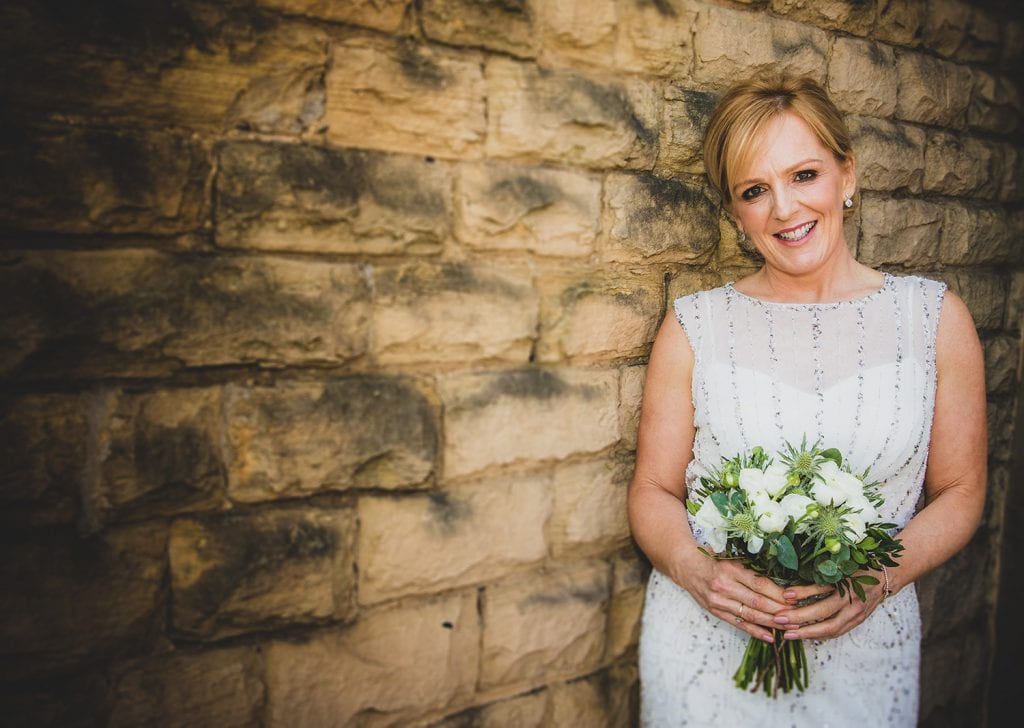 The bride posing against a stone wall