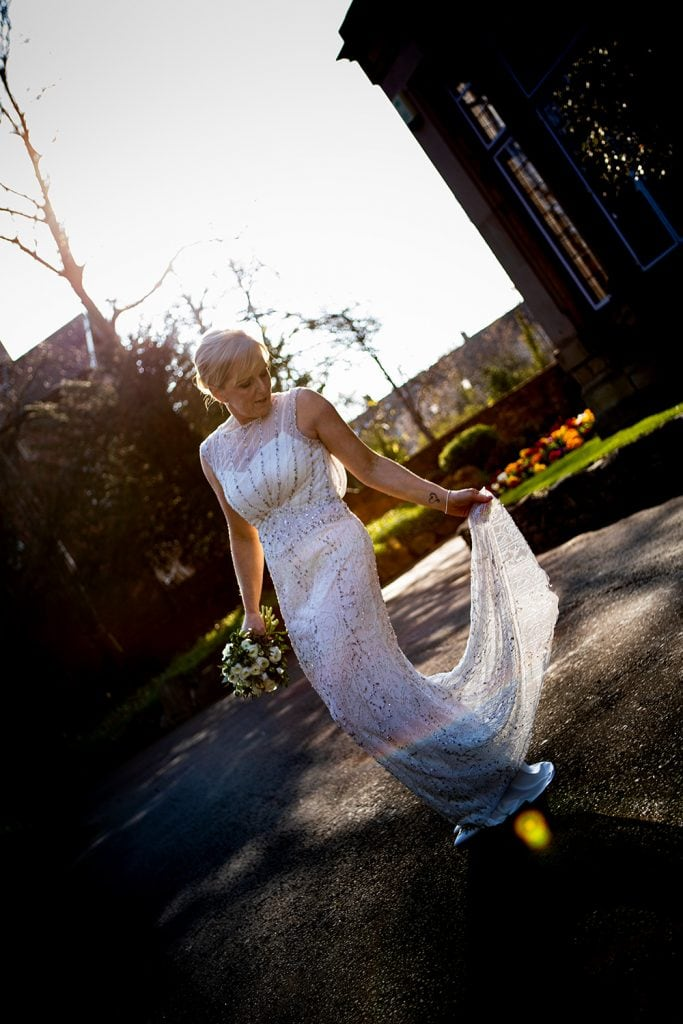 The bride adjusting her dress outside of The Mansion House in Jesmond, Newcastle