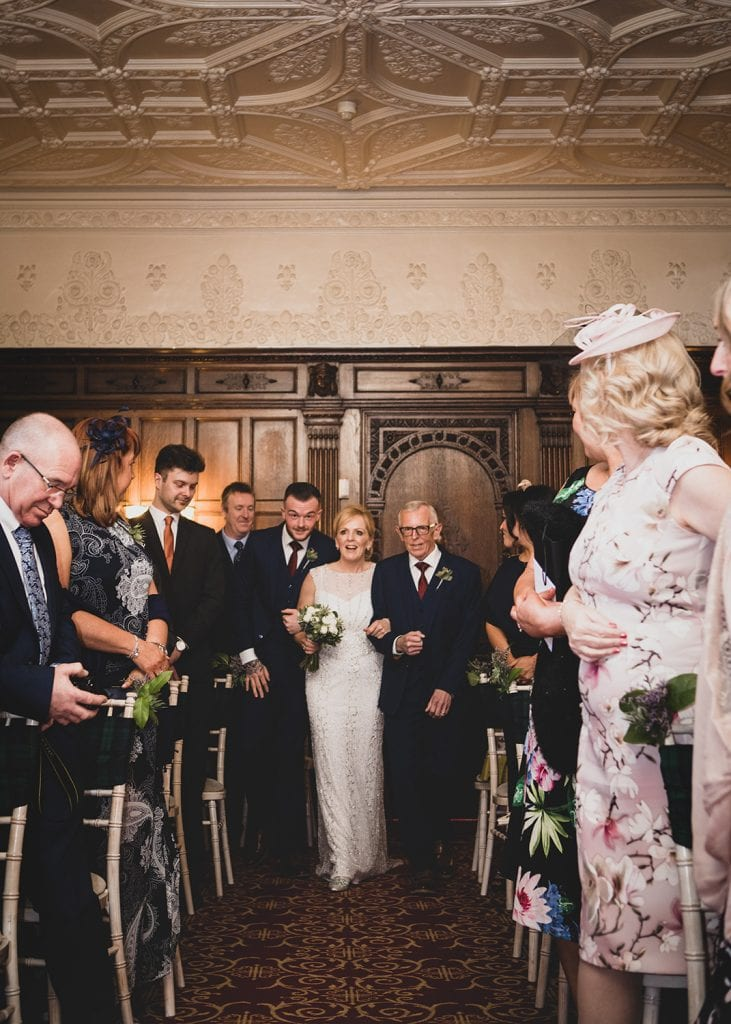The bride being escorted down the aisle at The Mansion House in Jesmond, Newcastle