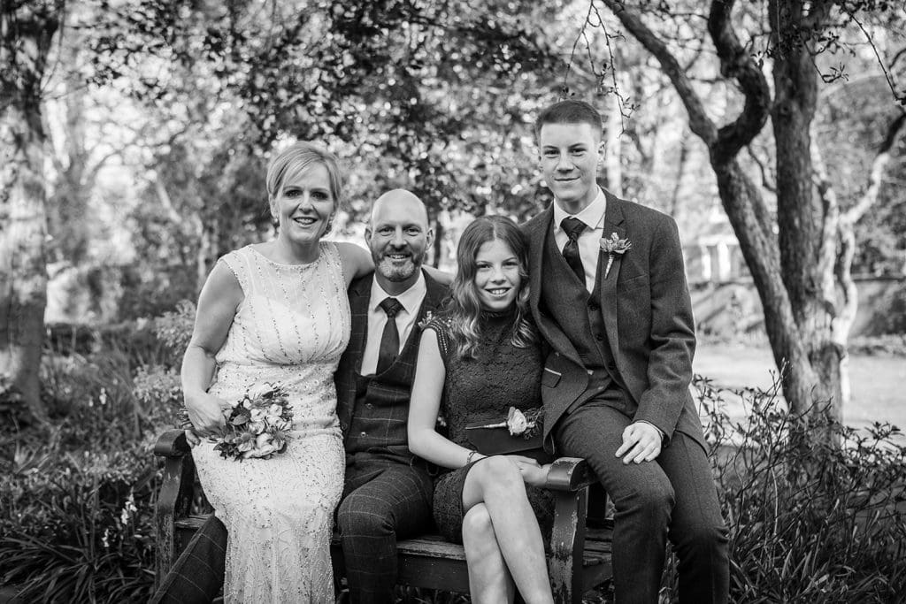 The Groom and his family sitting on a park bench at The Mansion House in Jesmond, Newcastle