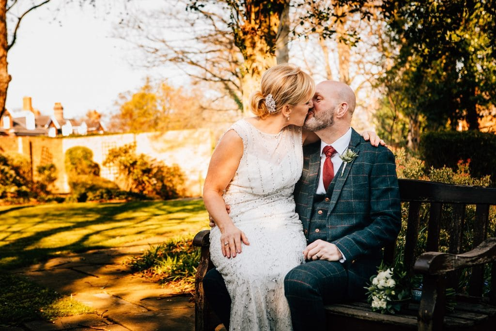 The bride & groom kissing on a park bench at The Mansion House in Jesmond, Newcastle
