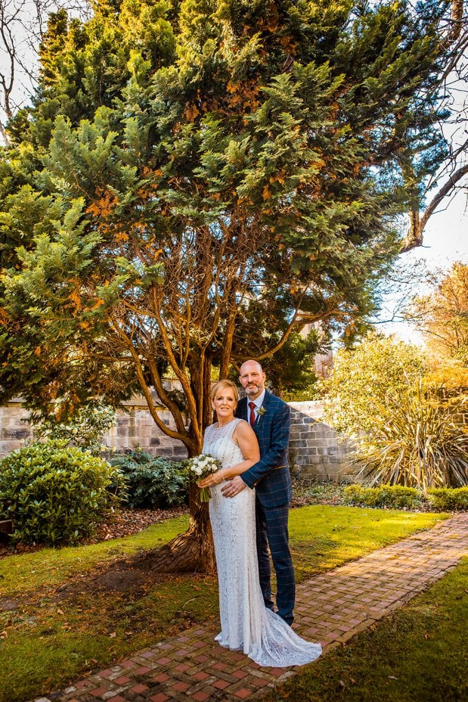 The bride & groom posing in the garden of The Mansion House in Jesmond, Newcastle
