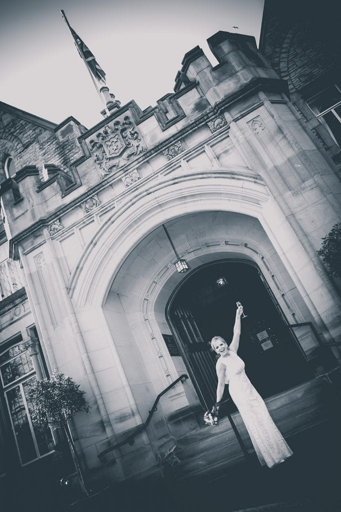 The bride celebrating outside the entrance of The Mansion House in Jesmond, Newcastle