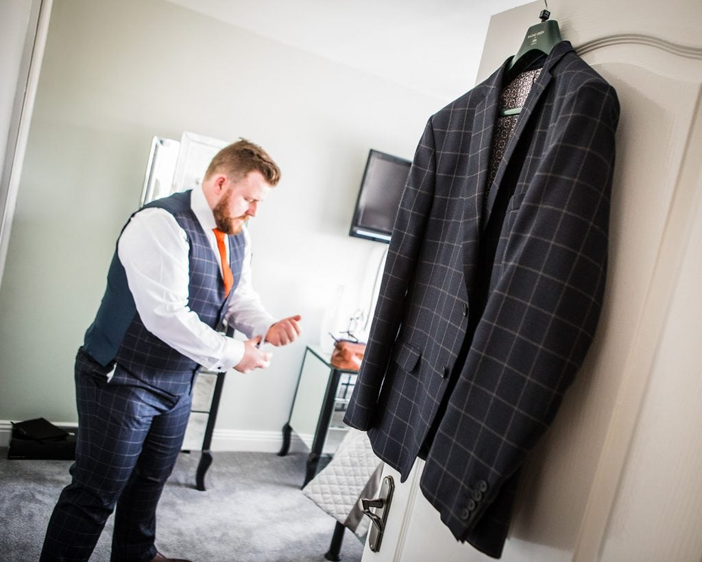 Groom getting ready with his jacket hanging on the door.