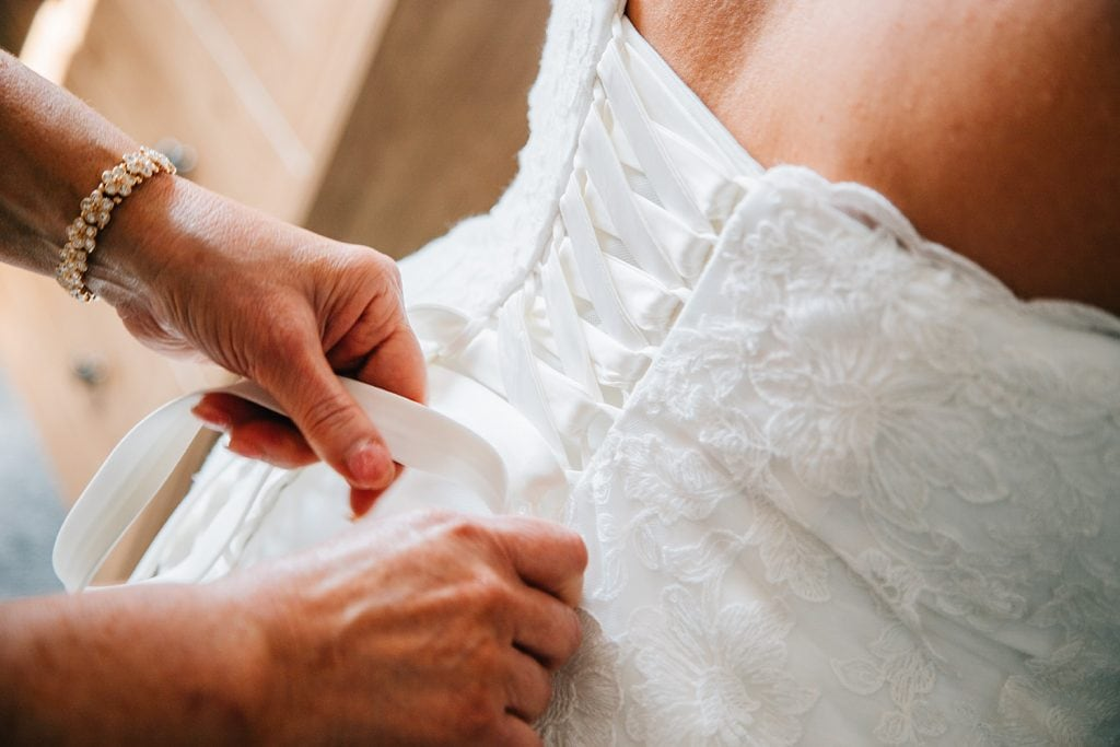 brides mum lacing her dress up