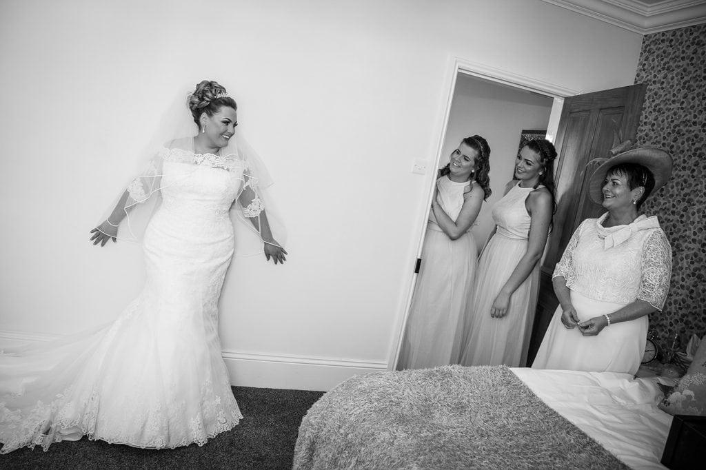Bride posing against bedroom wall
