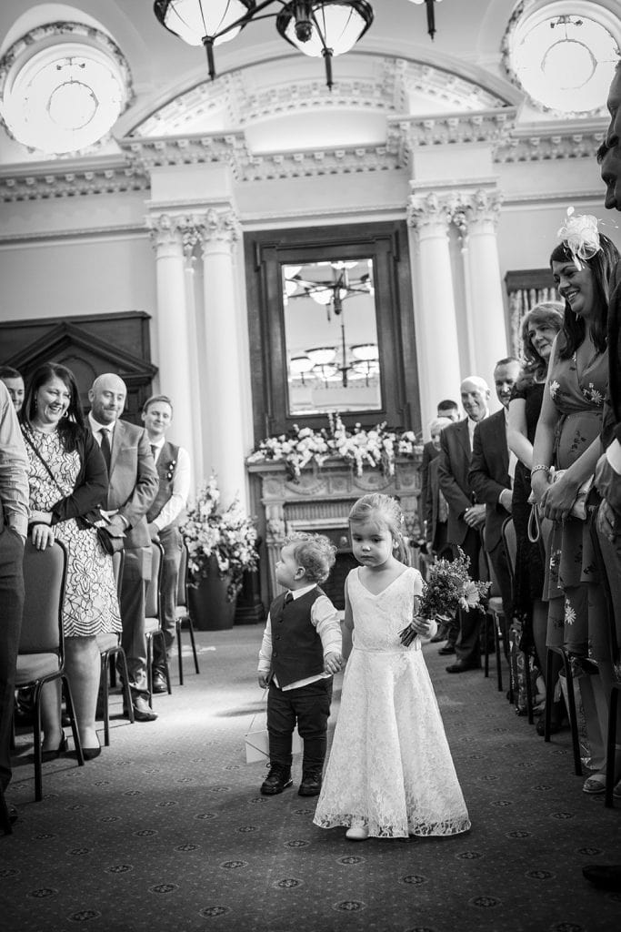 Flower Girl & Page Boy walking down the reception room aisle