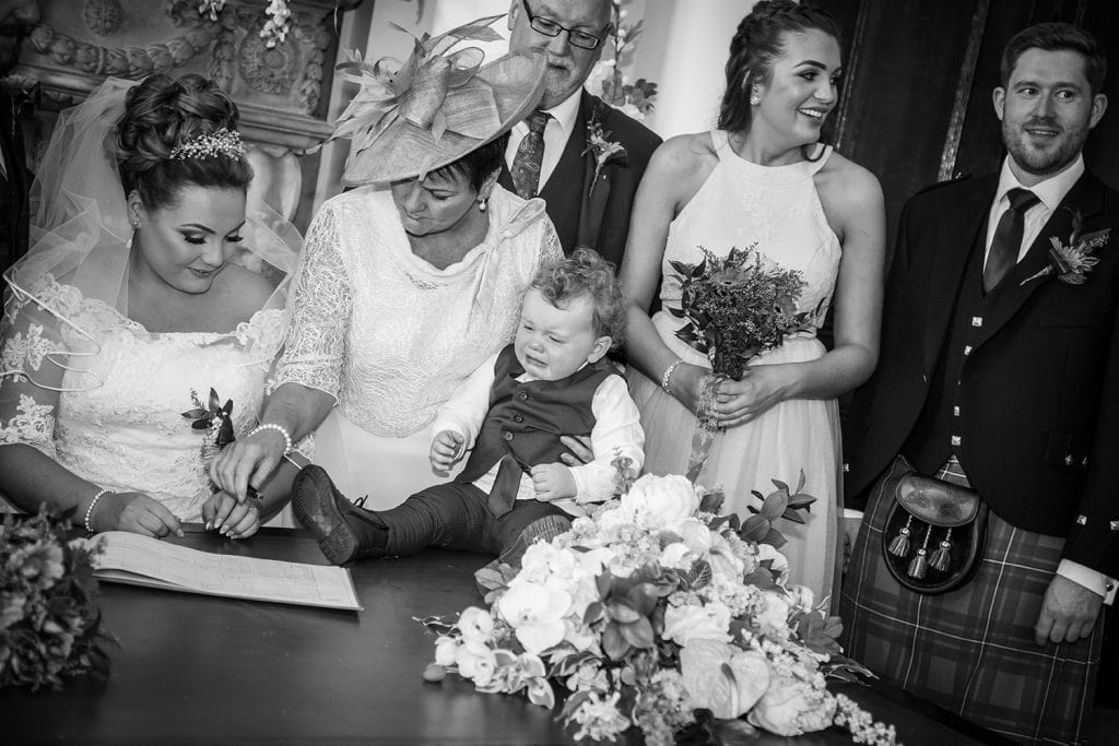 The page boy crying while bride signs the register