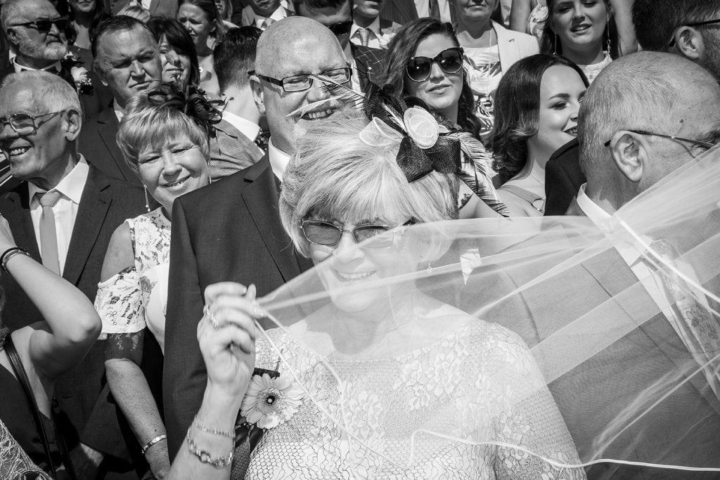 Grandmother hiding behind brides veil