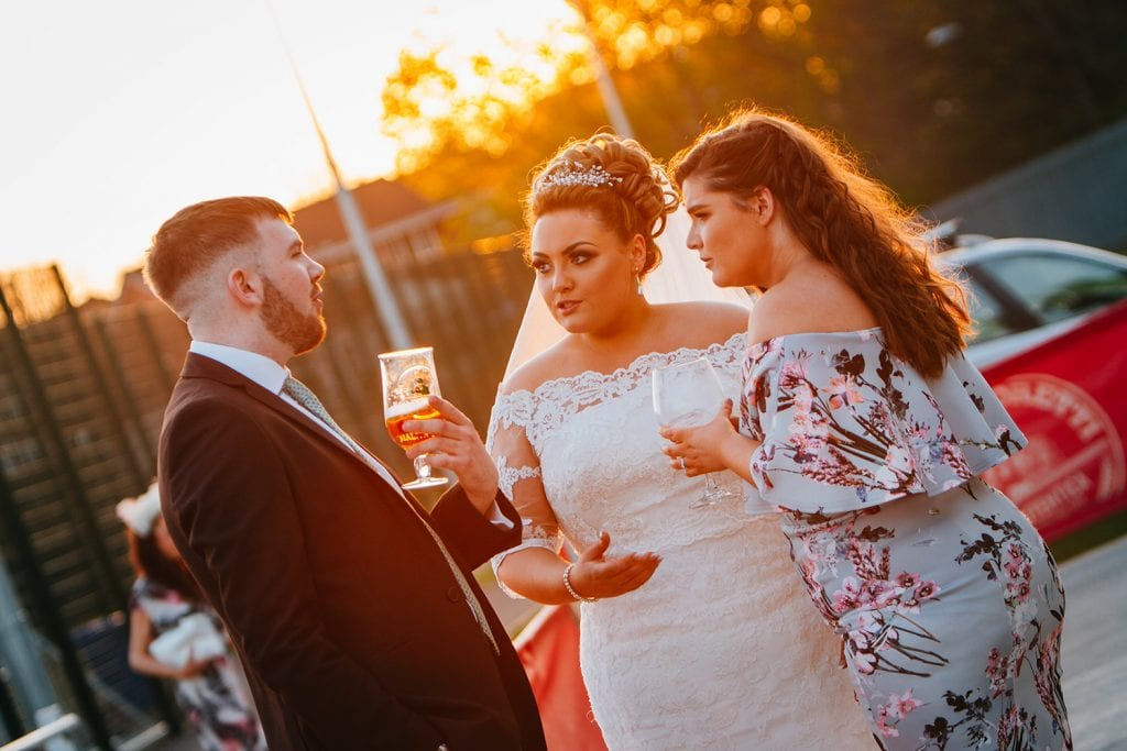 Bride talking to guests with the sunset behind at Guests relaxing in the sun at South Shields Football Club