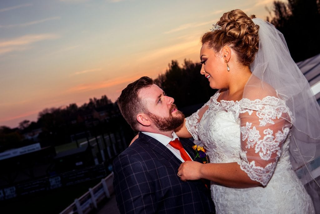 The bride & groom talking as the sun sets at South Shields Football Club