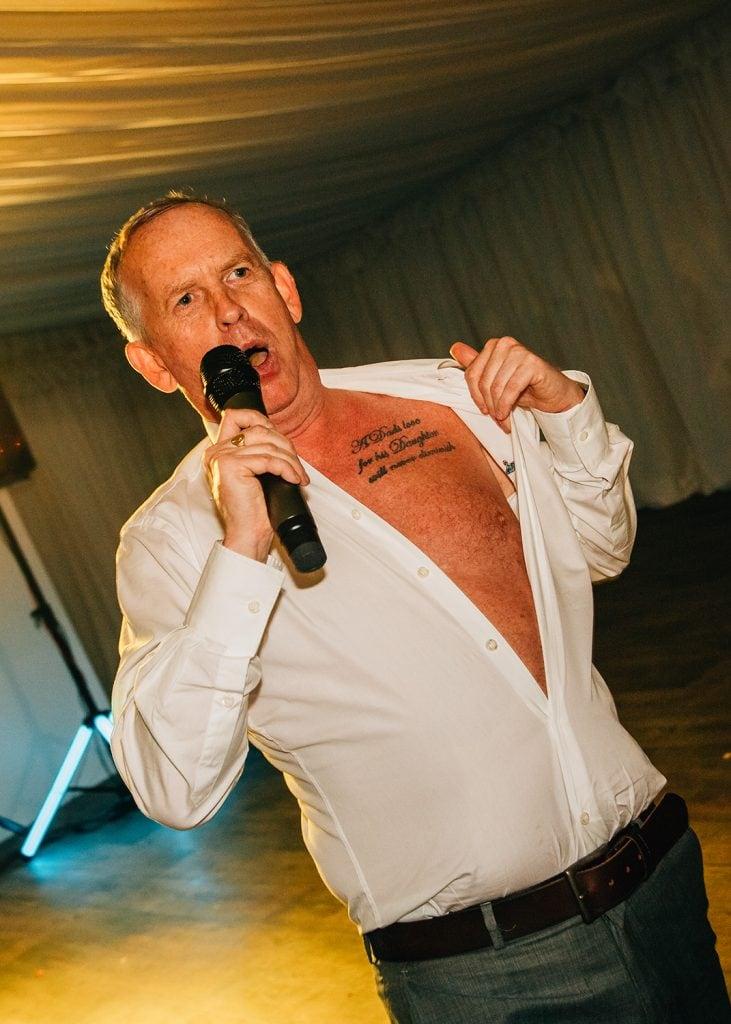 Guest flashing a tattoo while singing karaoke