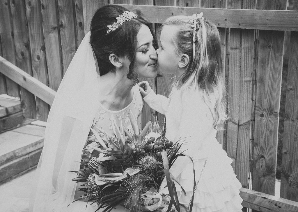 Bride getting a kiss from her flowergirl