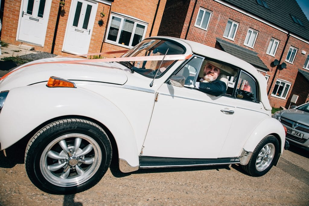 Brides Brother driving his white VW Beetle to the wedding