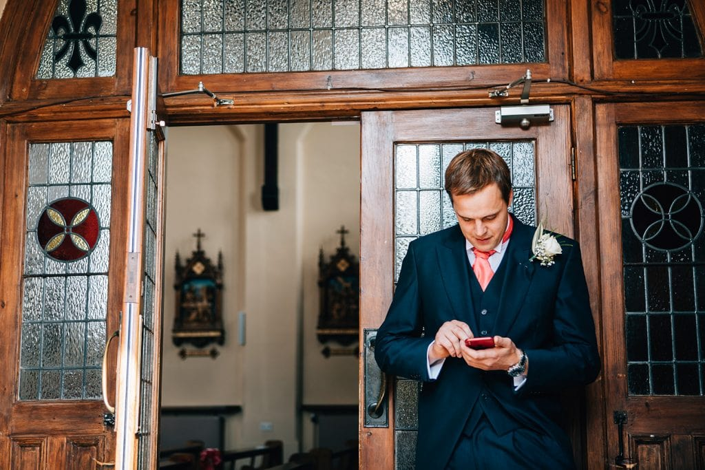 Groomsman trying to call the groom outside St Aidan's RC Church in Ashington