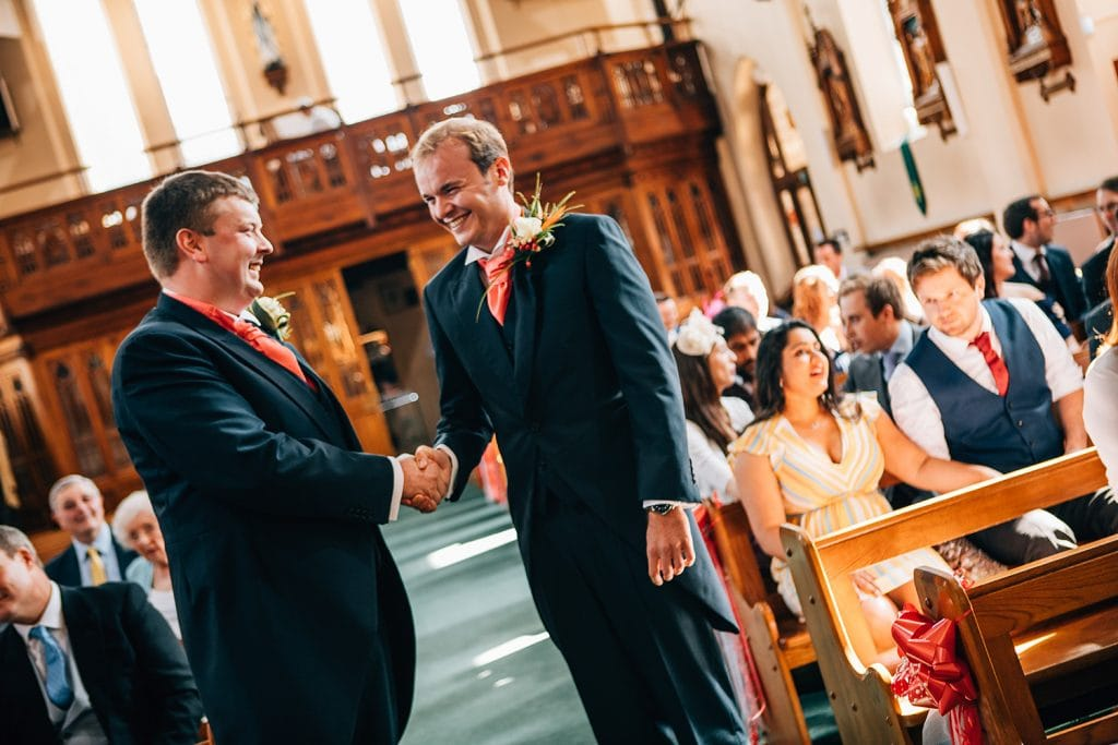 Bestman & groom shaking hands in St Aidan's RC Church in Ashington