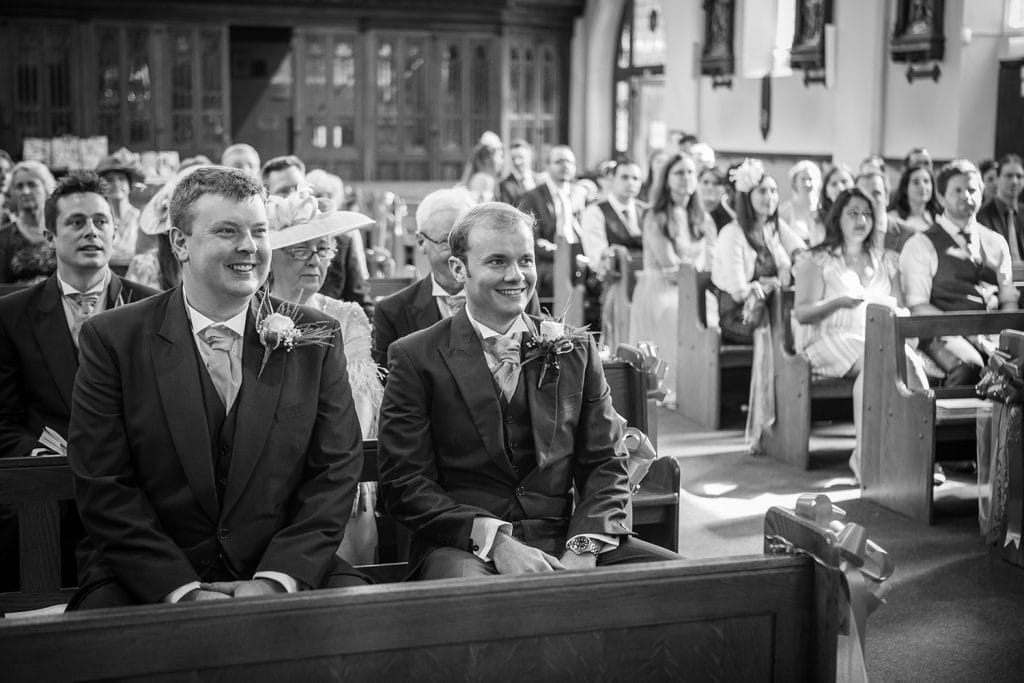 Groom & Bestman laughing at priests jokes in St Aidan's RC Church in Ashington