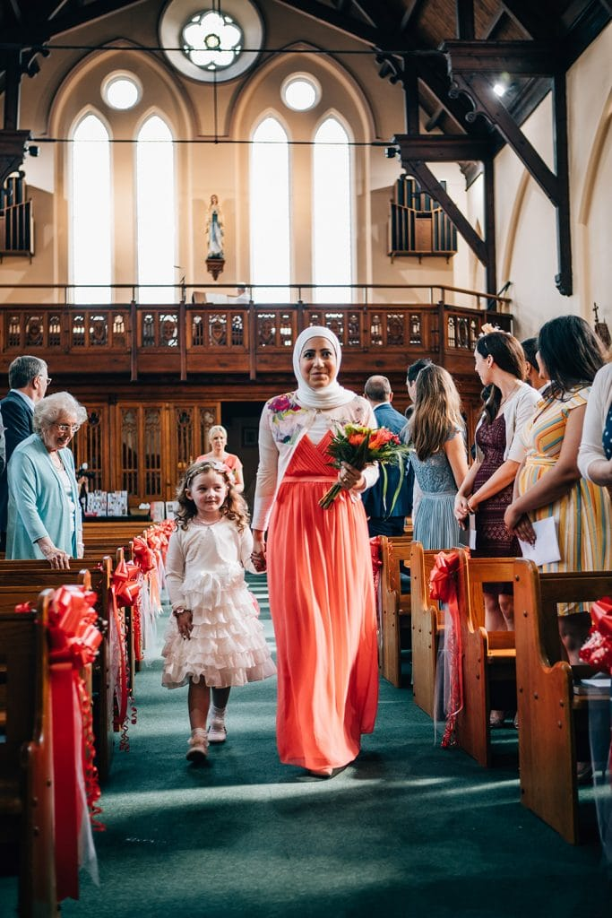 Bridesmaids walking down the aisle of St Aidan's RC Church in Ashington