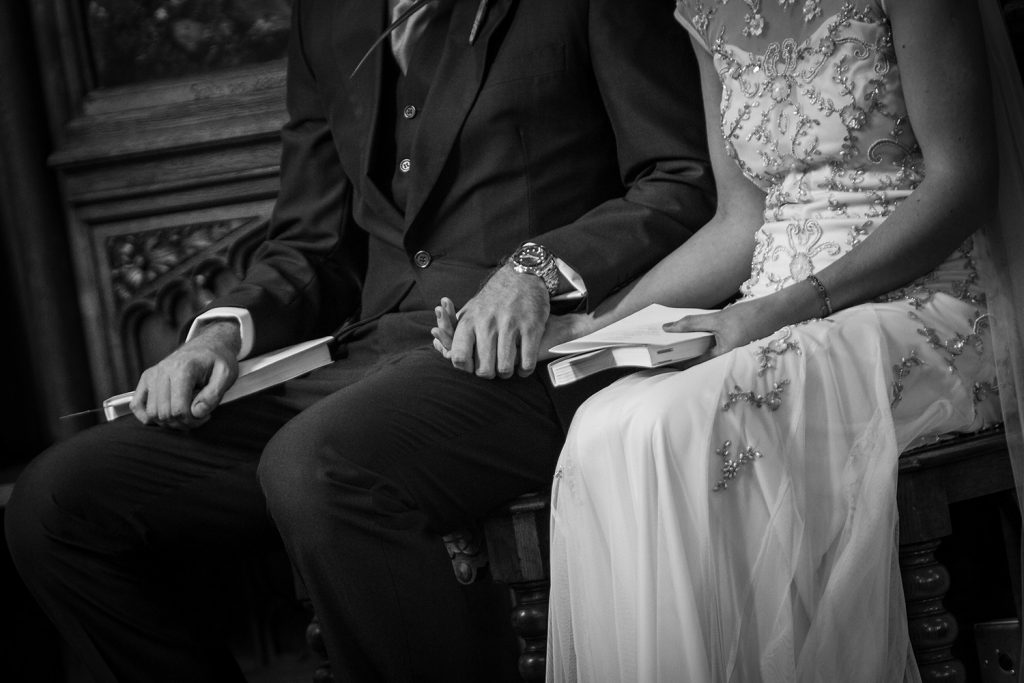 Bride & Groom holding hands in St Aidan's RC Church in Ashington