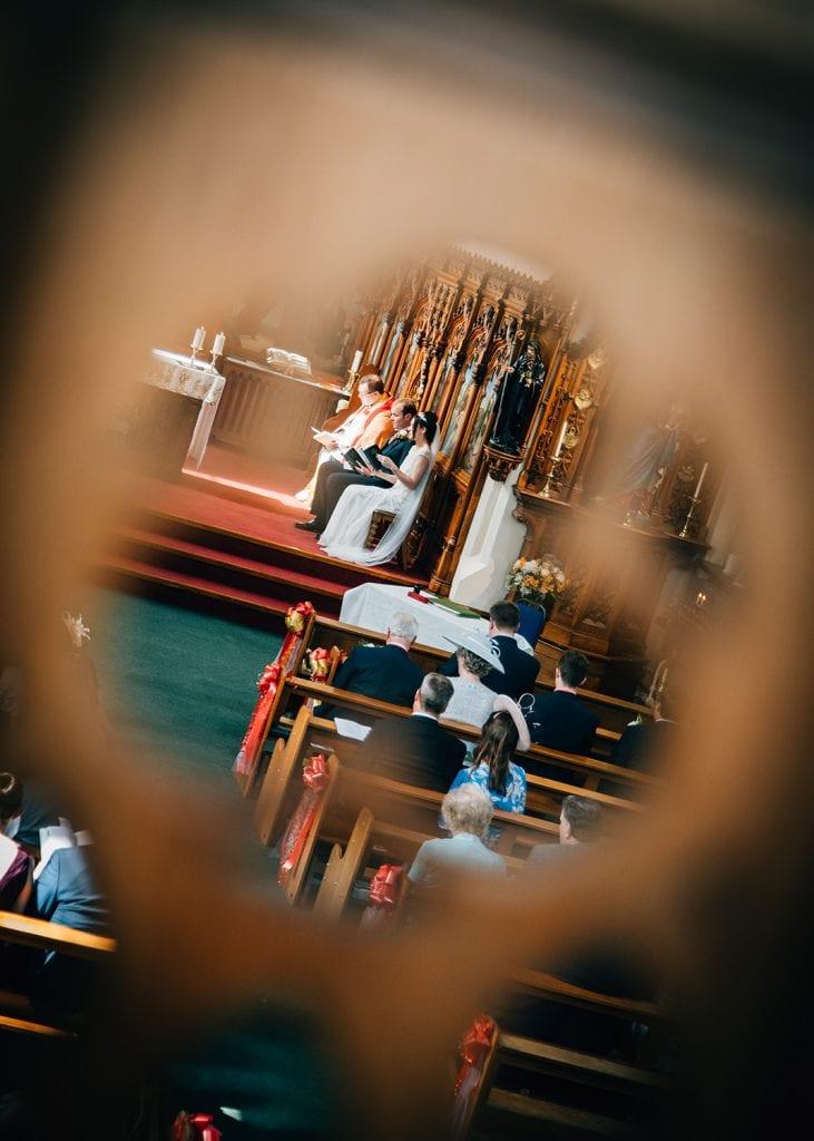 View of a wedding through a banister at St Aidan's RC Church in Ashington