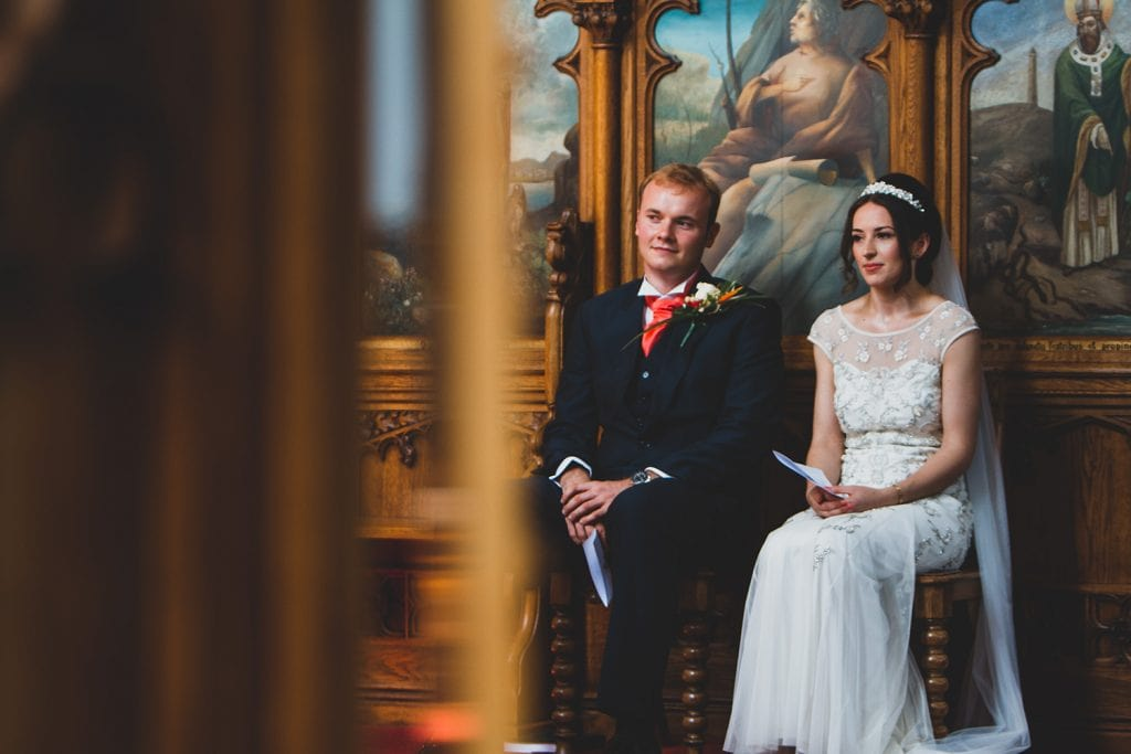 Mary & Alex in front of beautiful paneling in St Aidan's RC Church in Ashington