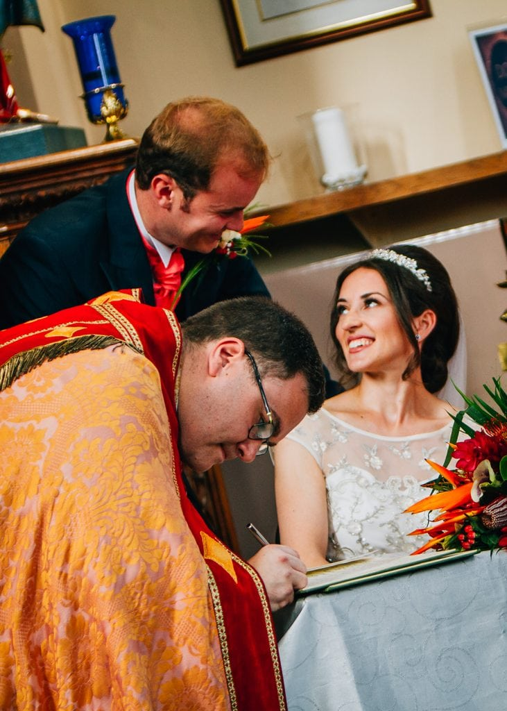 Alex & Mary laughing as preist signs the register at St Aidan's RC Church in Ashington
