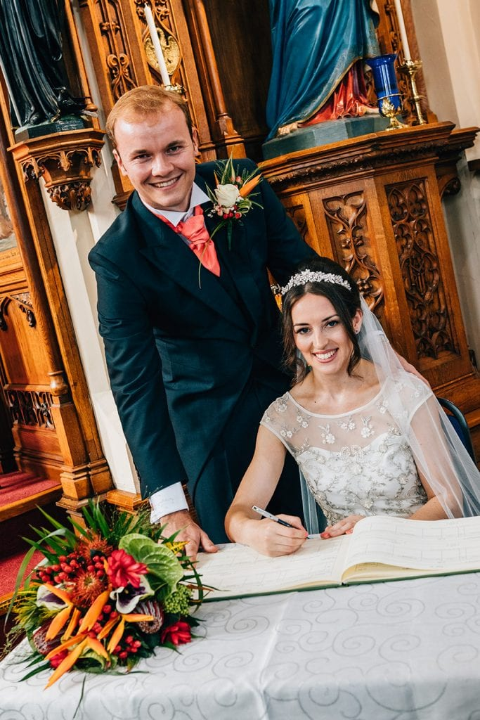 Mary & Alex signing the register at St Aidan's RC Church in Ashington