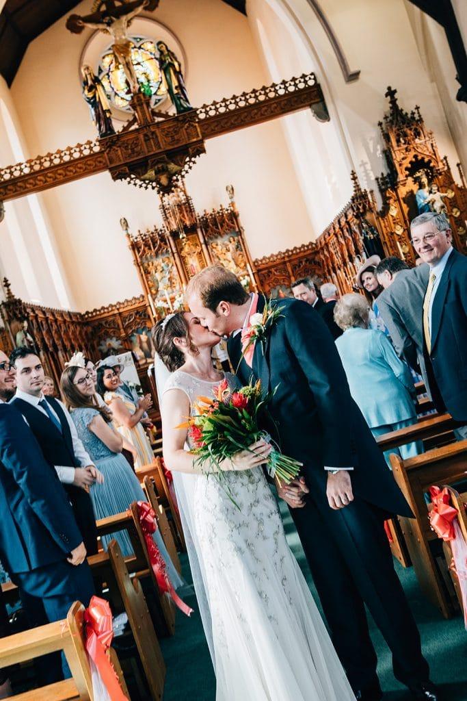 Mary & Alex kissing in the aisle of St Aidan's RC Church in Ashington